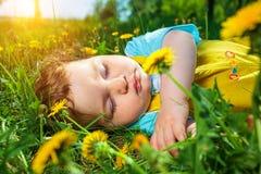 Garçon de sommeil sur l'herbe Photos stock