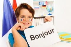 Garçon de sourire apprenant le français à la salle de classe Images libres de droits