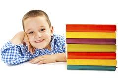 Garçon de sourire avec des livres d'école sur la table Image stock