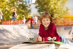 Garçon de sourire avec la pose verte de planche à roulettes Image libre de droits