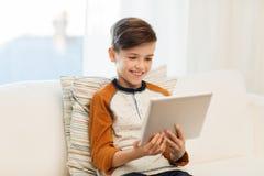 Garçon de sourire avec la tablette à la maison Photographie stock libre de droits
