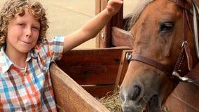 Garçon de sourire avec le cheval de alimentation banque de vidéos