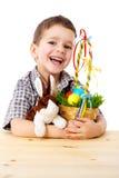 Garçon de sourire avec les oeufs et le lapin de pâques Image stock