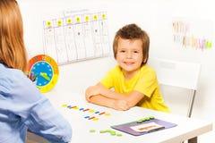 Garçon de sourire avec les pièces de monnaie colorées dans l'ordre Photo stock
