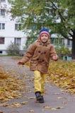 Garçon de sourire courant le long d'un chemin avec les feuilles jaunes sur un fond de fond image libre de droits