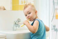 Garçon de sourire d'enfant d'enfant balayant et dents propres dans la salle de bains lui-même image stock