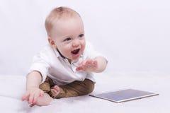 Garçon de sourire d'enfant en bas âge jouant avec un comprimé Photographie stock
