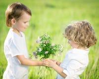 Garçon de sourire donnant le bouquet Images stock