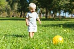 Garçon de sourire donnant un coup de pied une boule dans le jardin photographie stock