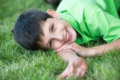 Garçon de sourire en vert sur le pré d'été photo stock