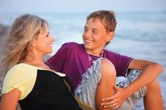 Garçon de sourire et jeune femme sur la plage en soirée Image libre de droits