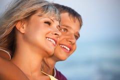 Garçon de sourire et jeune femme sur la plage en soirée Photos libres de droits