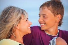 Garçon de sourire et jeune femme sur la plage en soirée Photos stock