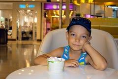 Garçon de sourire mangeant la crême glacée Photo stock