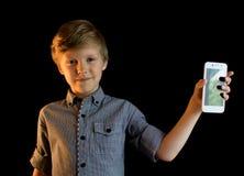 Garçon de sourire montrant le téléphone portable D'isolement regarder l'appareil-photo Images libres de droits