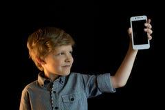 Garçon de sourire montrant le téléphone portable D'isolement regarder l'appareil-photo Photo stock