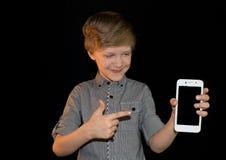 Garçon de sourire montrant le téléphone portable D'isolement regarder l'appareil-photo Image stock