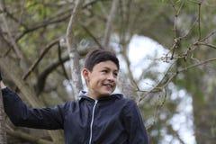 Garçon de sourire parmi les arbres Photographie stock libre de droits
