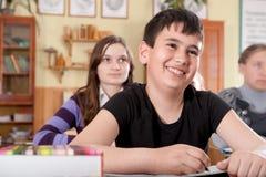 Garçon de sourire pendant la leçon à l'école Photo stock