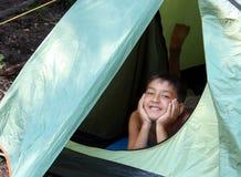 Garçon de sourire regardant de la tente Images stock