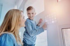 Garçon de sourire regardant sa mère tout en touchant un dispositif sur le mur Photo stock