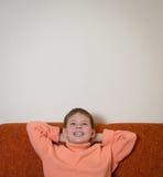 Garçon de sourire s'asseyant sur le sofa et rêver Enfant recherchant et détendant à la maison le Copie-espace Image libre de droits