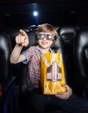 Garçon de sourire se dirigeant tout en observant le film 3D Images libres de droits