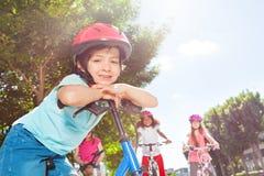 Garçon de sourire se tenant avec la bicyclette au parc d'été Image libre de droits
