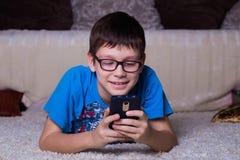 garçon de sourire se trouvant sur le plancher faisant face à la caméra et à regarder le smartphone images stock