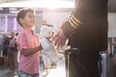 Garçon de sourire sincère donnant le jouet pilote Photographie stock