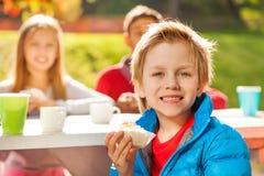 Garçon de sourire tenant le petit gâteau avec ses amis Photo stock