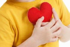 Garçon de sourire tenant une figurine rouge de coeur symbole de l'amour, famille, Concept de la famille et des enfants Images stock