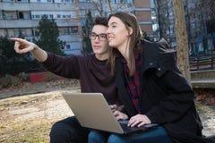 Garçon de Stydent montrant une fille sur un ami Photographie stock libre de droits