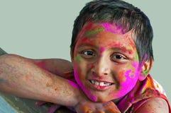 Garçon de visage de plan rapproché jeune jouant des couleurs de sourire de Holi Photo stock