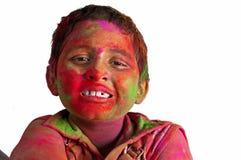 Garçon de visage de plan rapproché jeune jouant des couleurs de sourire de Holi Photos stock