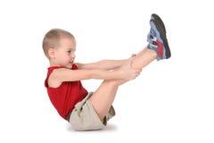 Garçon de yoga avec des pattes vers le haut Image stock