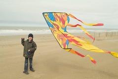 Garçon de Yong jouant avec son cerf-volant sur la plage Photos libres de droits
