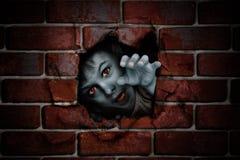 Garçon de zombi jetant un coup d'oeil hors d'un trou dans un mur images stock