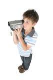 Garçon debout à l'aide d'une caméra vidéo digitale image libre de droits