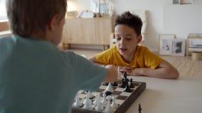 Garçon deux jouant aux échecs dans la chambre légère Deux frères jouant aux échecs banque de vidéos