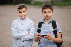 Garçon deux s'asseyant sur les jeux sur Internet de banc et de jeu Garçons un avec le sac à dos Les jeunes garçons utilisent leur photographie stock libre de droits