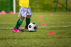 Garçon donnant un coup de pied le ballon de football sur le champ de sports Trainin du football du football Photographie stock