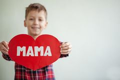 Garçon doux mignon avec le coeur de papier rouge sur le fond Coeur pour la mère image libre de droits