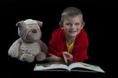 Garçon drôle avec un chien bourré lisant un livre pendant le temps de lit Images stock