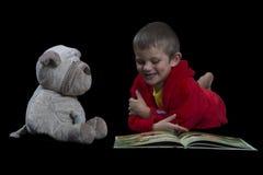 Garçon drôle avec un chien bourré lisant un livre pendant le temps de lit Photo libre de droits