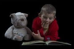 Garçon drôle avec un chien bourré lisant un livre pendant le temps de lit Photographie stock