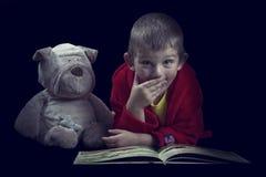 Garçon drôle avec un chien bourré lisant un livre pendant le temps de lit dans l'arti Image stock