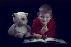 Garçon drôle avec un chien bourré lisant un livre pendant le temps de lit dans l'arti Photo stock