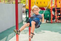 Garçon drôle d'enfant ayant l'amusement avec l'oscillation à chaînes sur le terrain de jeu extérieur Photographie stock libre de droits