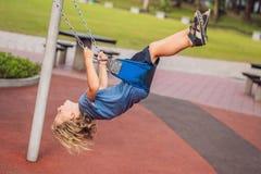 Garçon drôle d'enfant ayant l'amusement avec l'oscillation à chaînes sur le terrain de jeu extérieur Images libres de droits